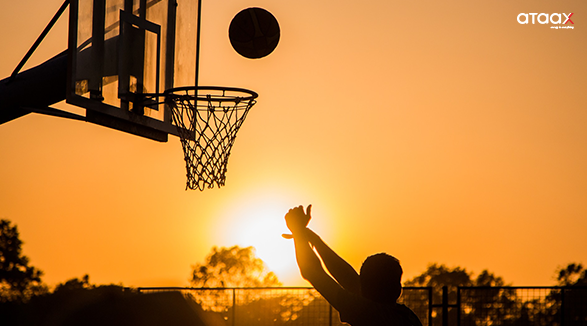 Basketball hoop and ball during sunset